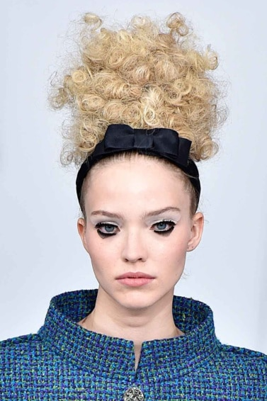 blonde model at the chanel couture aw16 show with a curly updo and a black bow headband