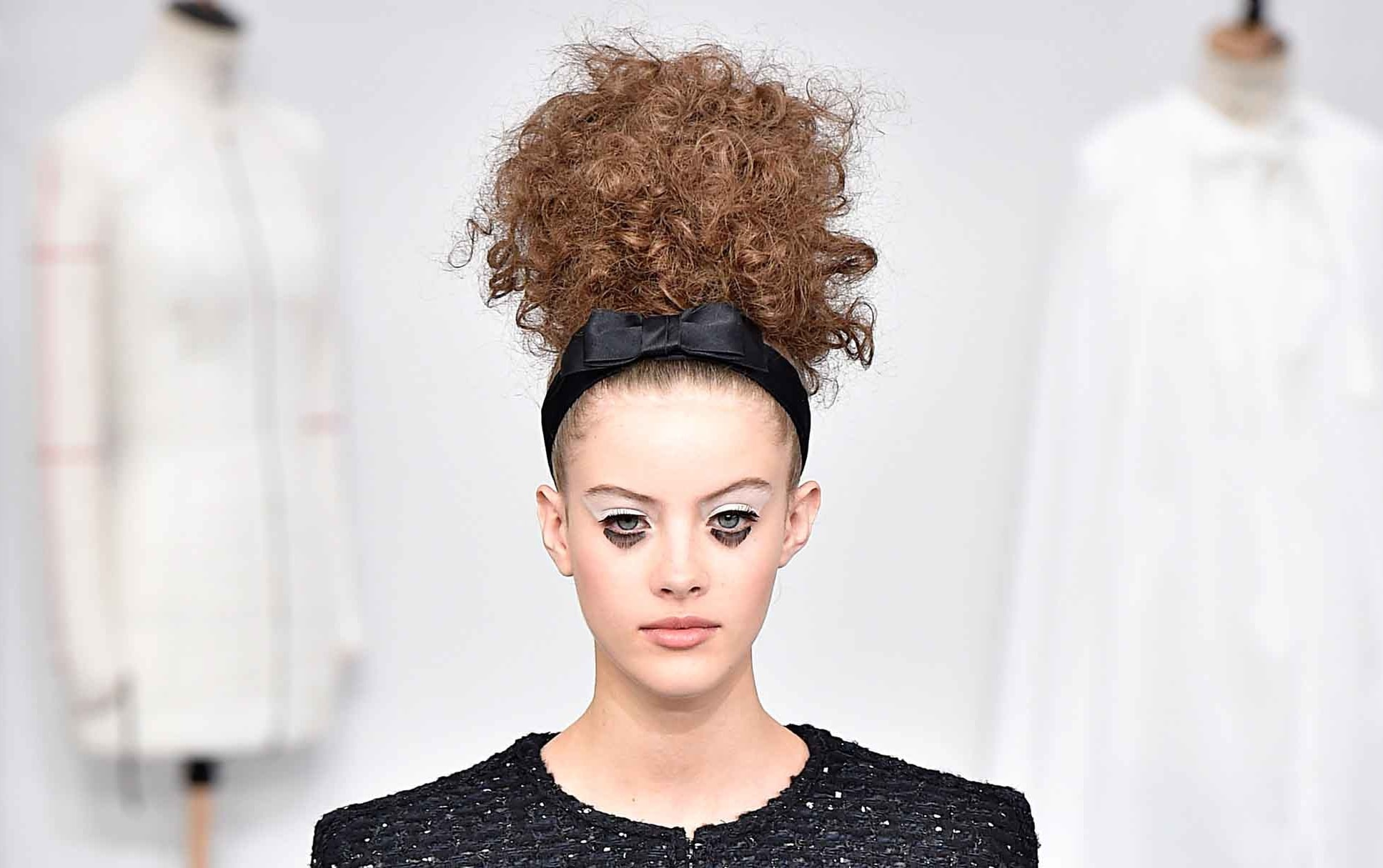 brunette chanel couture model wearing a black bow headband