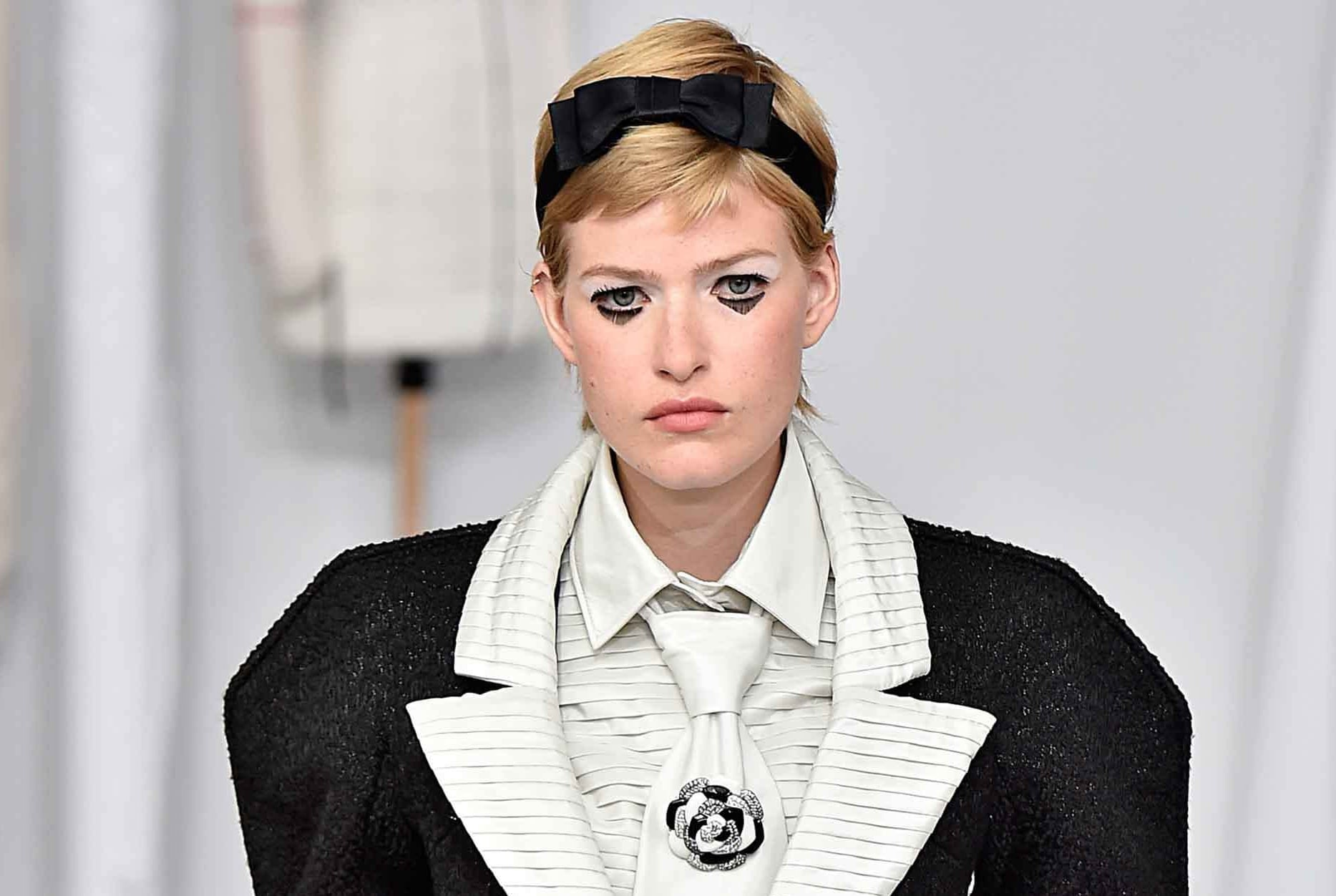 chanel couture aw16 model with a blonde pixie mullet and a black bow headband