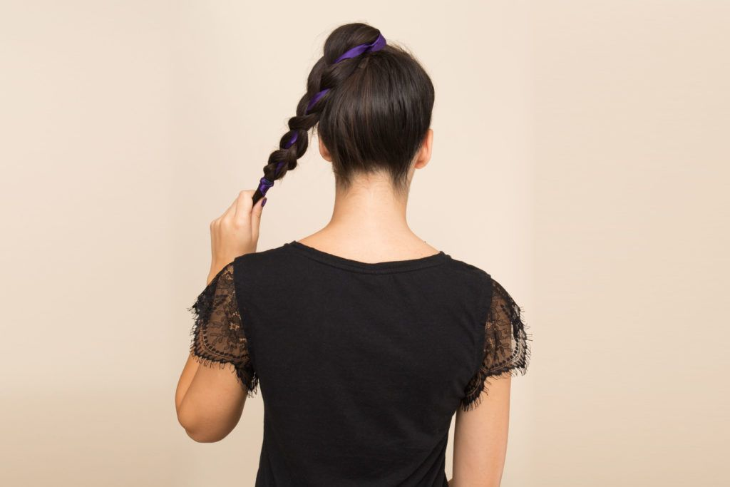 model wearing cute ponytail with woven ribbon on medium length brown hair model