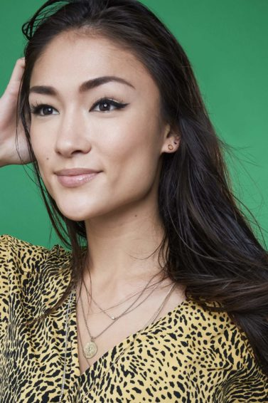 asian model wearing a yellow animal print top with long dark straight hair