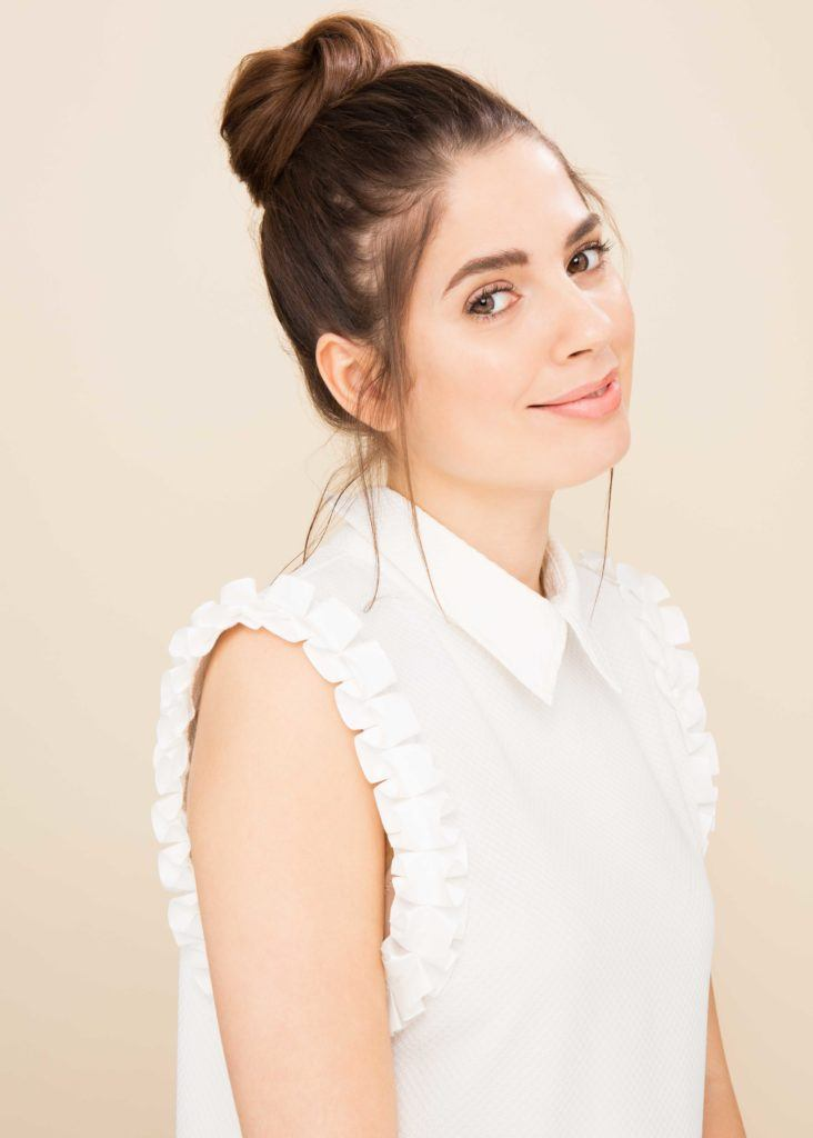model with brown hair in high top knot wearing sleeveless white shirt