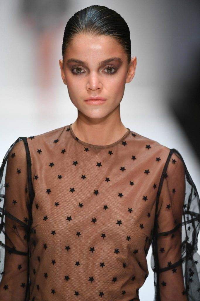 woman on catwalk with brown wet look smooth low bun wearing black sheer spotted dress
