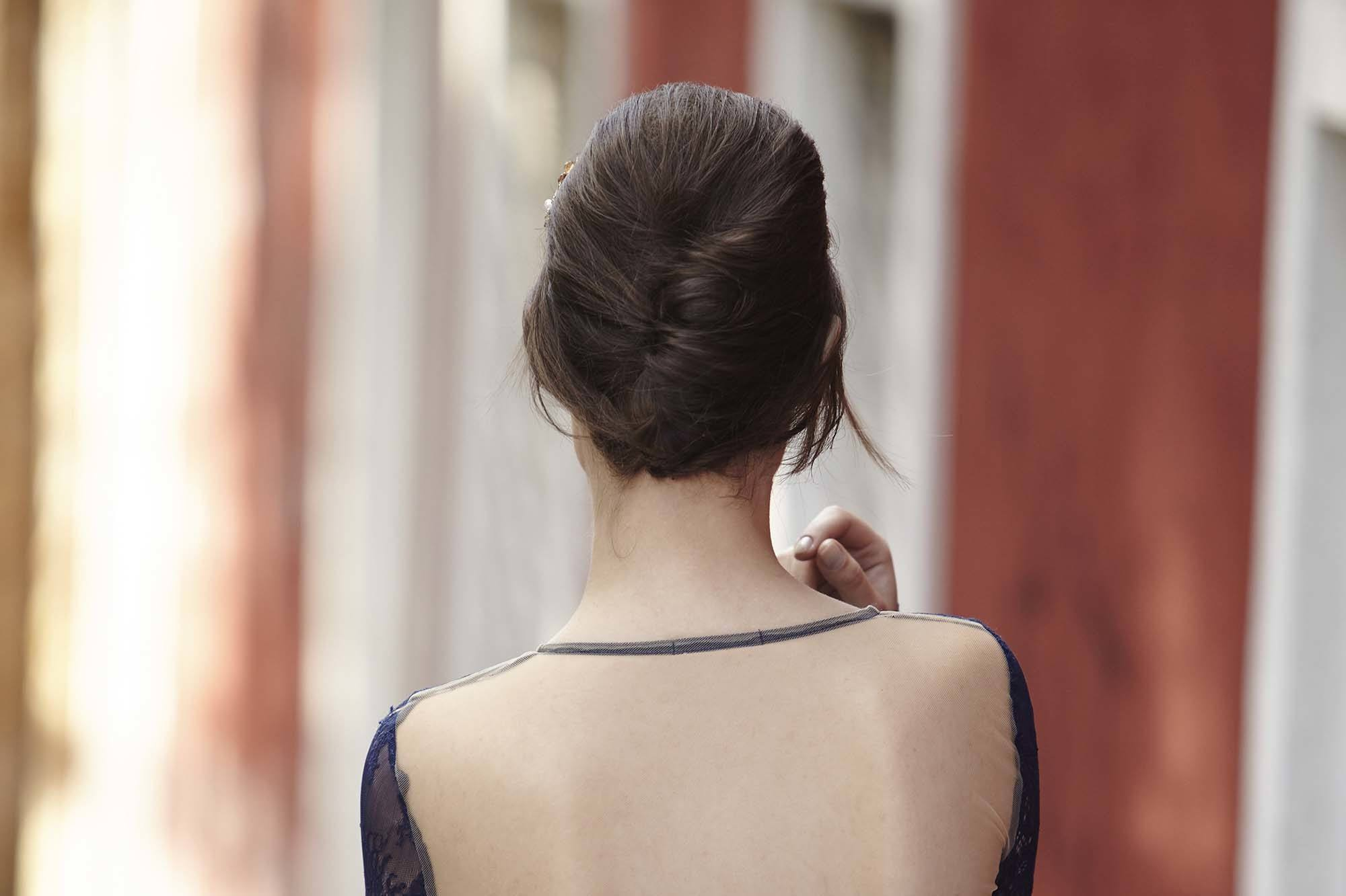 Vintage hairstyles for long hair: Back shot of a woman with long dark chocolate hair styled into a French twist updo wearing a blue dress and posing outside