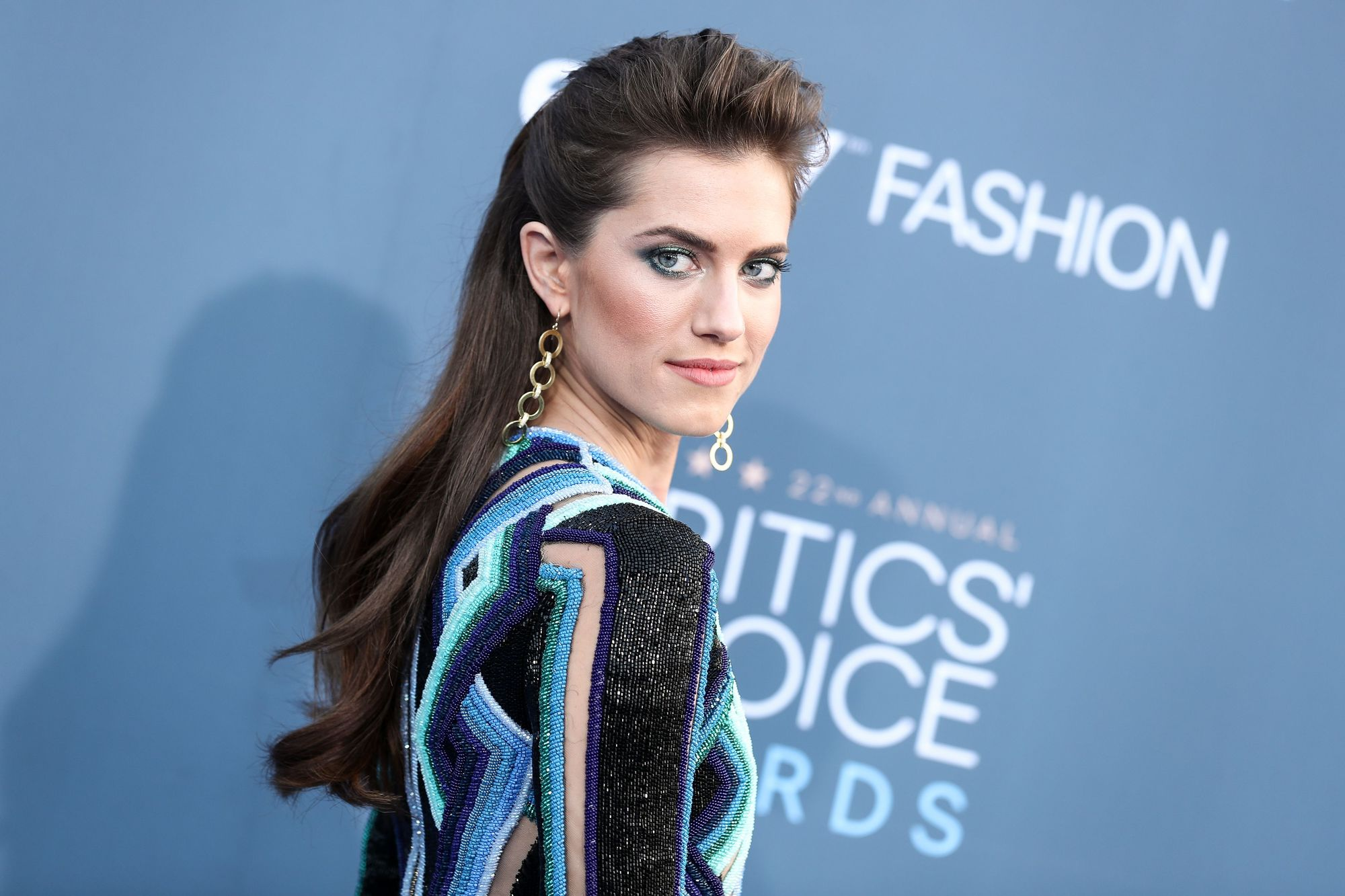 Vintage hairstyles for long hair: Close up shot of Allison Williams with long chocolate brown hair styled into a half-up, half-down quiff hairstyle on the red carpet
