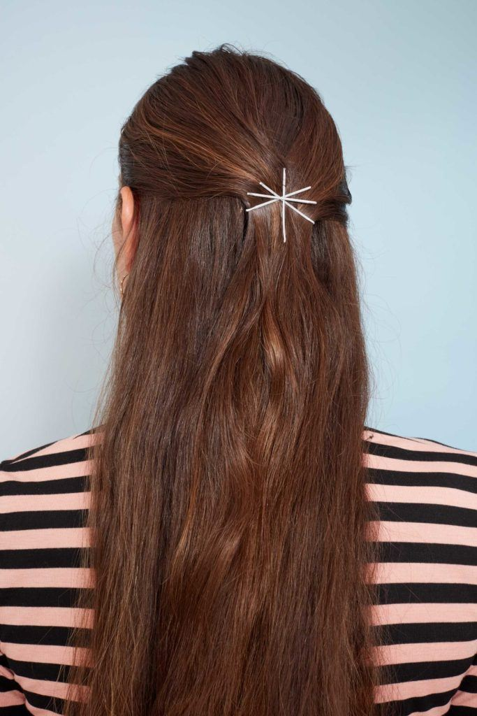 Bobby pin hairstyles: Close up shot of a woman with long chestnut brown hair styled into a half-up, half-down look and secured with bobby pins fashioned into an asterisk