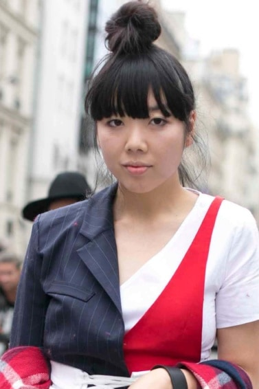 Susie Lau at couture week 2016 wearing a red white and navy outfit with her hair worn in a high bun with a fringe