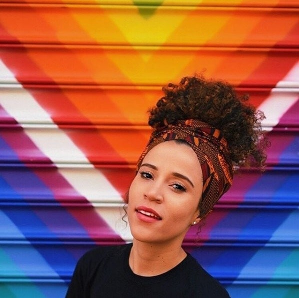 woman with natural curly hair tied up with a patterned silk head scarf standign in front of a rainbow wall