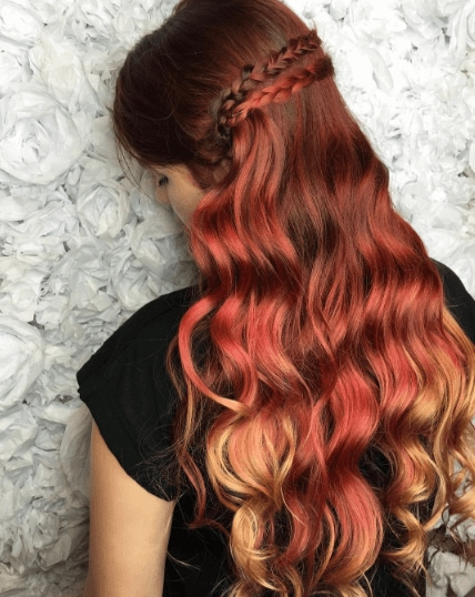 hairstyles for wavy hair: woman with long red dyed hair with waves and two briads