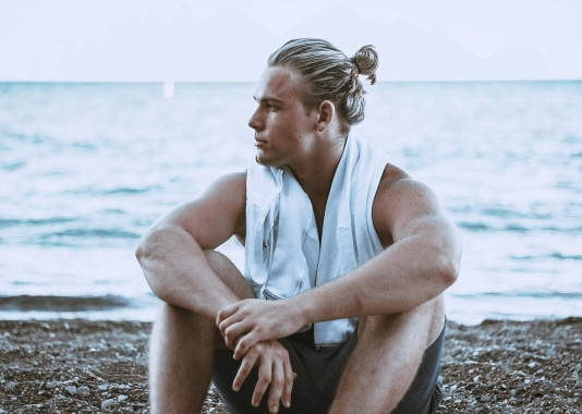 front view of a man sitting on the beach with blonde hair in a man bun