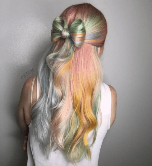 hairstyles for wavy hair: back view of woman with pastel coloured hair and a half up bow made from hair