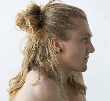 side view of a man with blonde hair in a half up man bun hairstyle