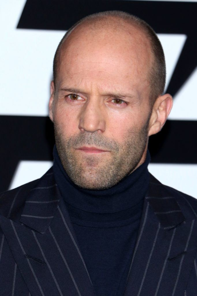 Hairstyles for receding hairline: Close-up headshot of Jason Statham with shaved head and