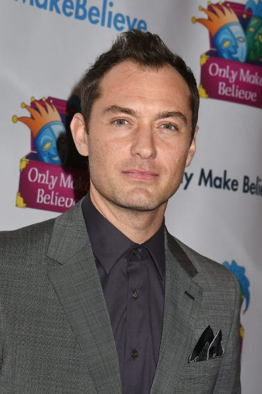 Hairstyles for receding hairline: Jude Law with brown hair in a mohawk style, wearing a grey suit