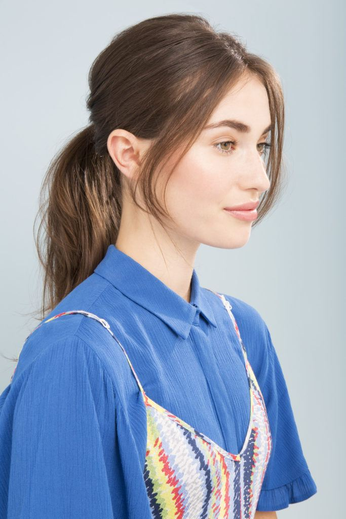 model with long straight brown hair in low messy ponytail with long pieces of hair hang loose at the front
