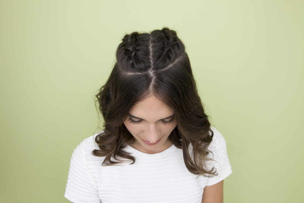 How to do a braid: model shows how to do braids in her dark hair with half up half down french braids