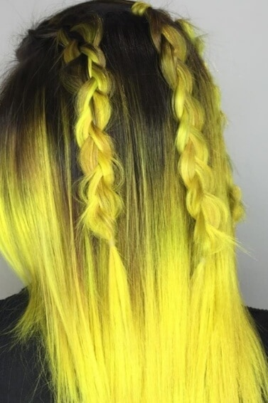 back view of a woman with bright yellow ombre hair with dark roots and two braids