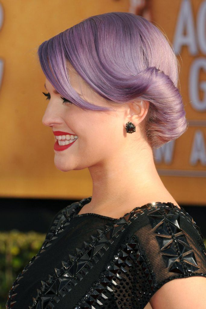 Vintage hairstyles for long hair: Close up shot of Kelly Osbourne with long lilac hair styled into a low rolled updo, wearing black and posing on the red carpet