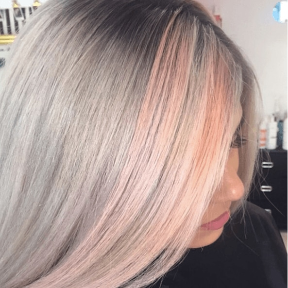 Shades of blonde hair: Woman with straight stray grey and pink pastel hair.