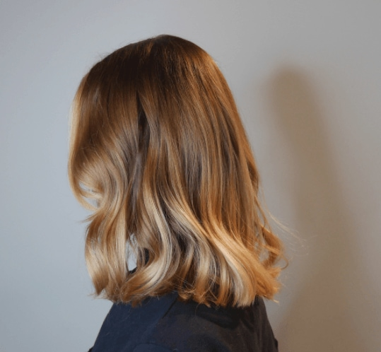 side view of a woman's shoulder length hair with waves and different shades of blonde