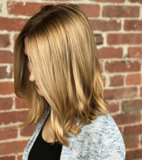 Shades of blonde hair: Woman with toffee blonde shoulder length hair with a slight wave.