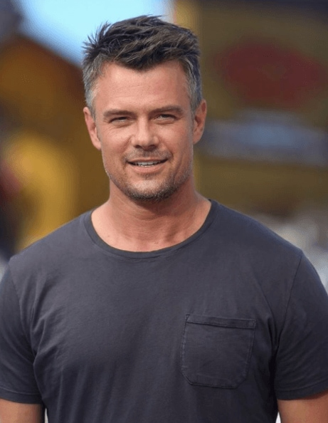 man with short hair and grey and balck colouring wearing a deep grey t shirt
