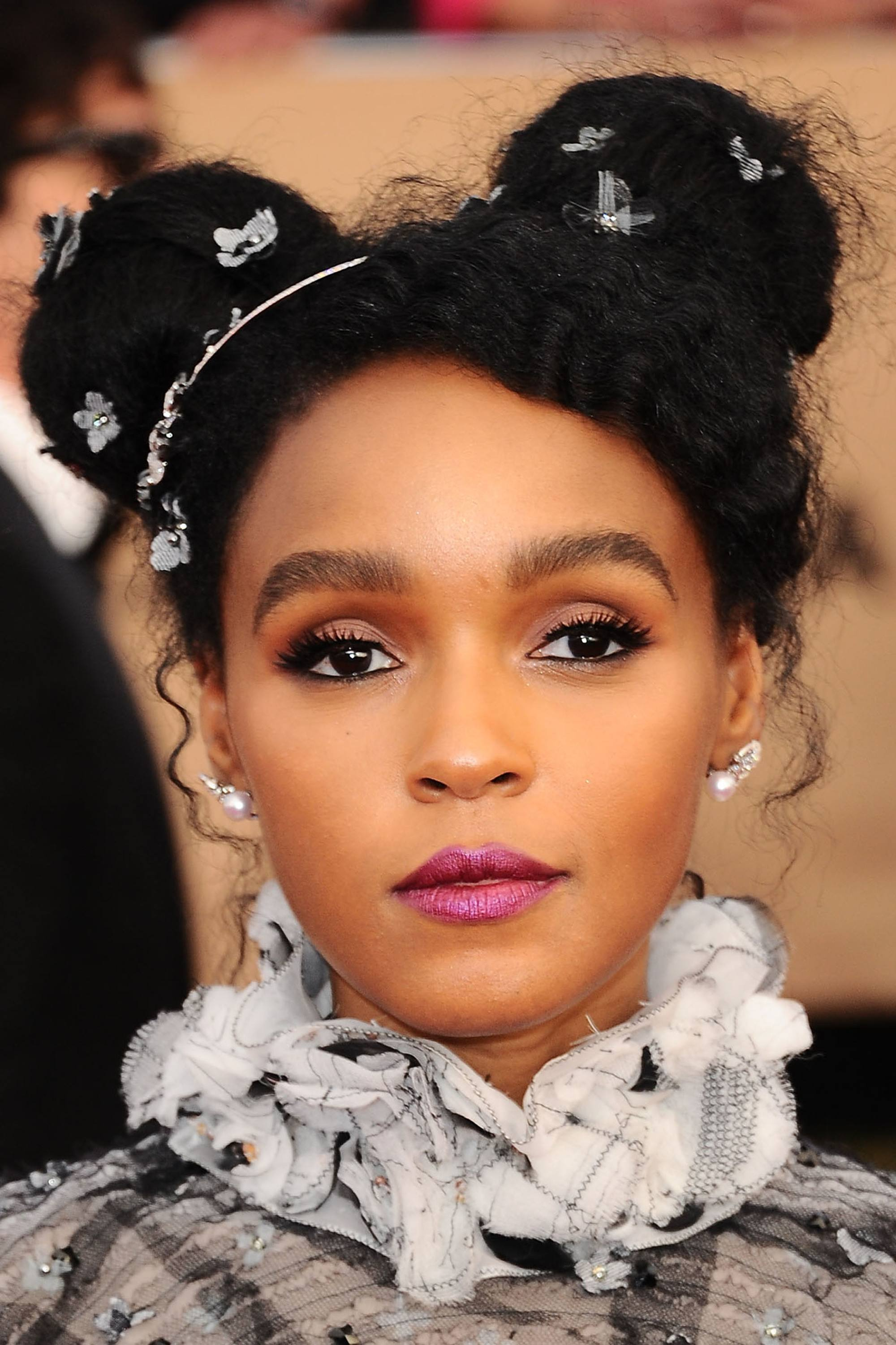 janelle monae at industry red carpet event with dark brown hair in space buns with jewelled accessories
