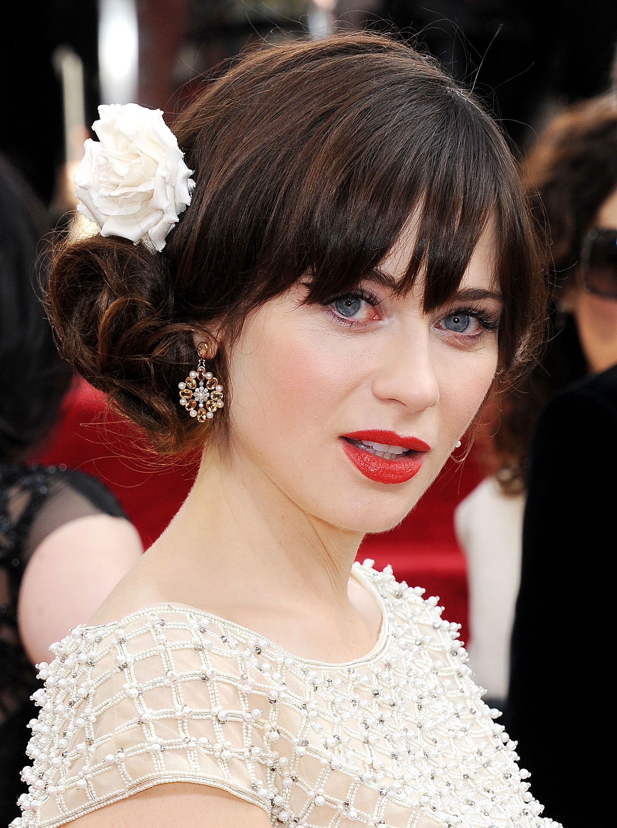 Vintage hairstyles for long hair: Close up shot of Zooey Deschanel with chocolate brown hair and fringe styled into a vintage low side bun with a floral barrette, wearing white on the red carpet