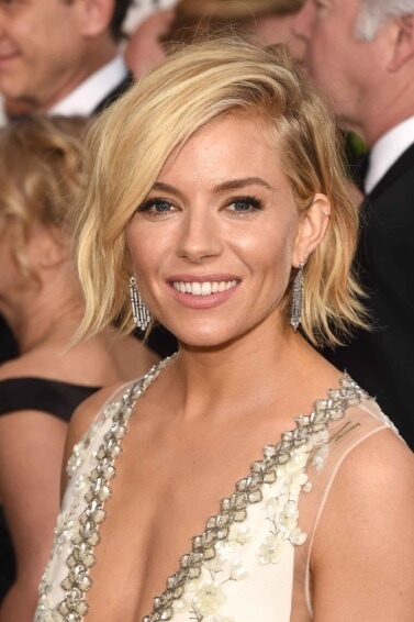 wavy blonde bob on Sienna Miller wearing a white and silver dress with droplet earrings in the red carpet