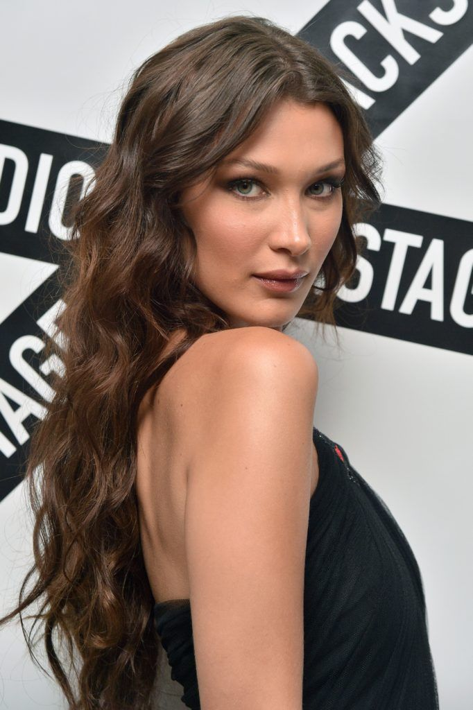 Vintage hairstyles for long hair: Close up shot of Bella Hadid with long chocolate brown hair styled into loose waves and curls on the red carpet