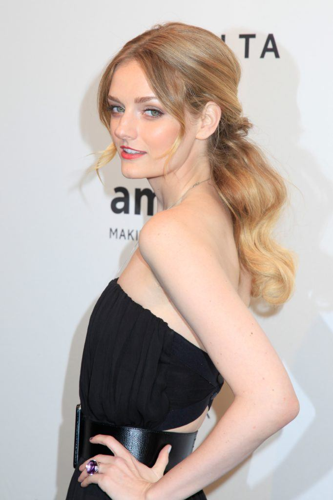 Vintage hairstyles for long hair: Close up shot of Lydia Hearst-Shaw with a teased ponytail, wearing a black dress and posing on the red carpet