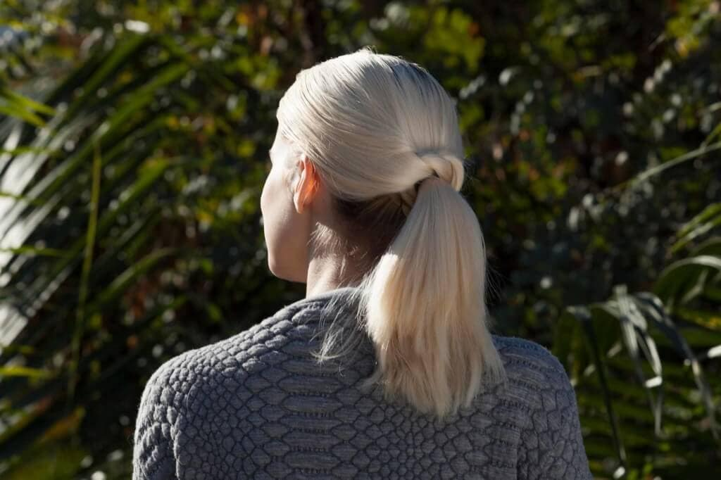 model with platinum blonde hair and a twisted ponytail