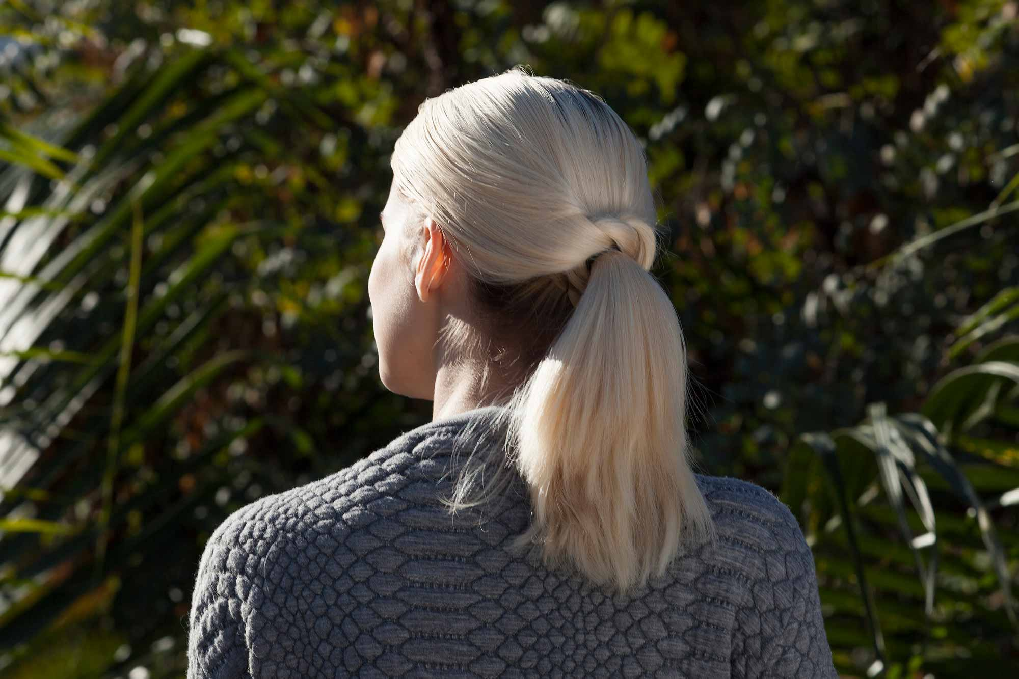 model with platinum blonde hair and a twisted ponytail hairstyle