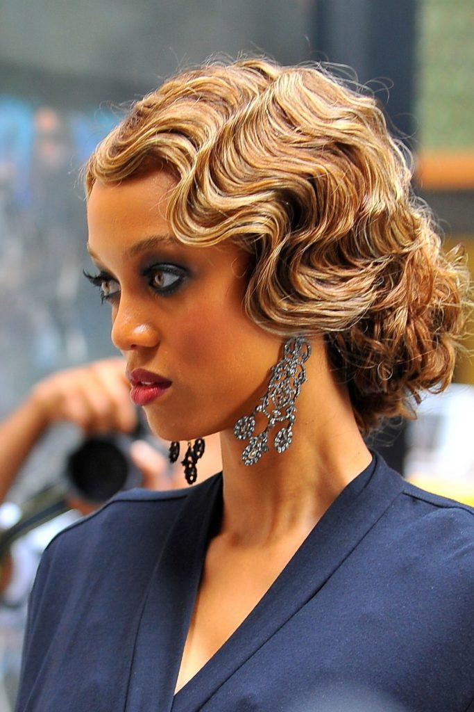 Vintage hairstyles for long hair: Close up shot of Tyra Banks with long caramel brown hair styled into a finger wave bun updo, wearing blue on the set of Gossip Girl
