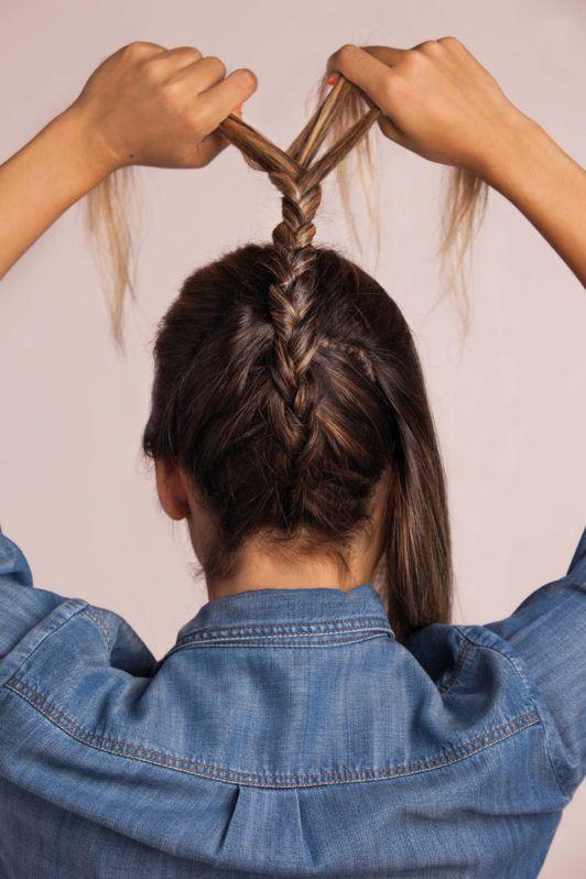 How to do a braided top knots: blonde woman braiding wavy hair wearing a denim shirt