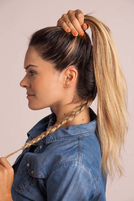 braided top knot bun: blonde woman holding a braid at the bottom and holding half her hair into a high ponytail wearing a denim shirt
