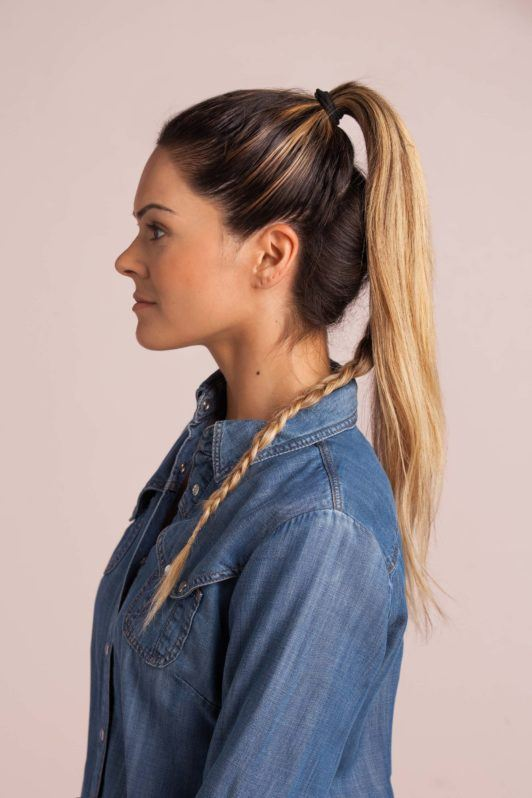 braid top knot: blonde woman with a braid at the bottom and holding half her hair into a high ponytail wearing a denim shirt