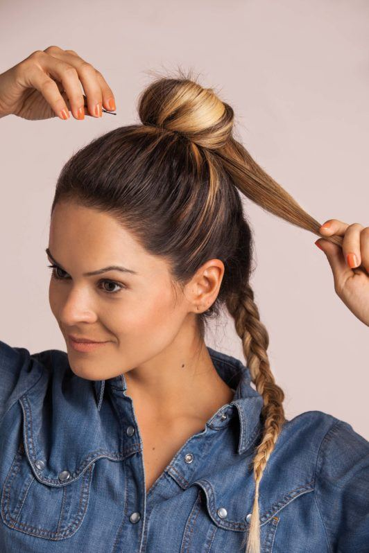 French braid into a top knot: blonde woman with a braid creating a bun