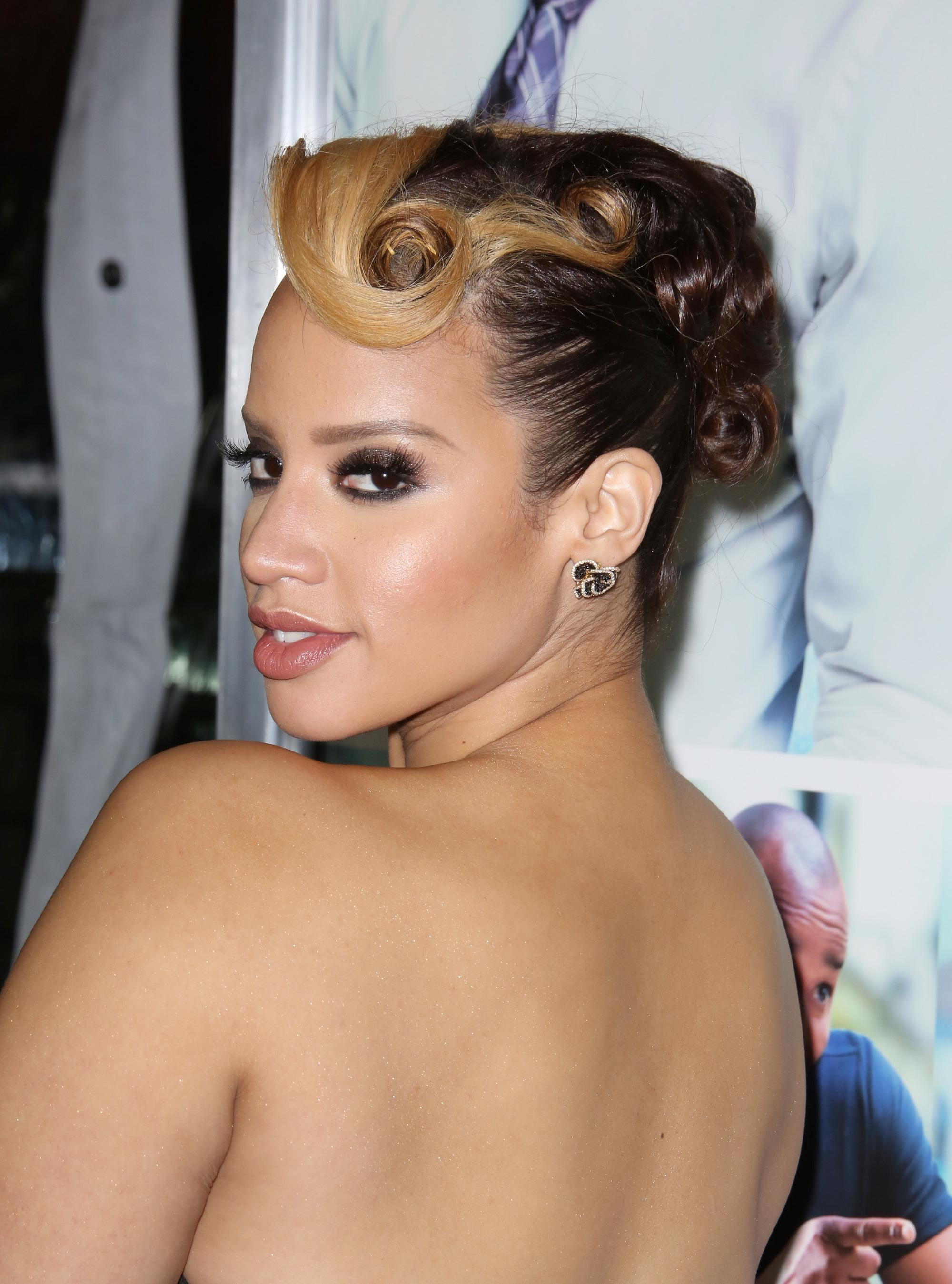 Vintage hairstyles for long hair: Close up shot of Dascha Polanco with two-tone caramel blonde and brown hair styled into an updo on the red carpet