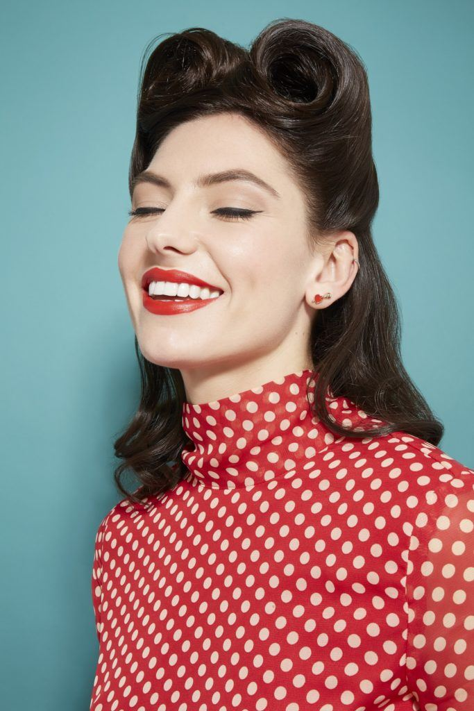 Vintage hairstyles for long hair: Close up shot of a model with long dark brown hair styled into a half-up victory roll hairstyle, wearing a polka dot dress in a studio setting