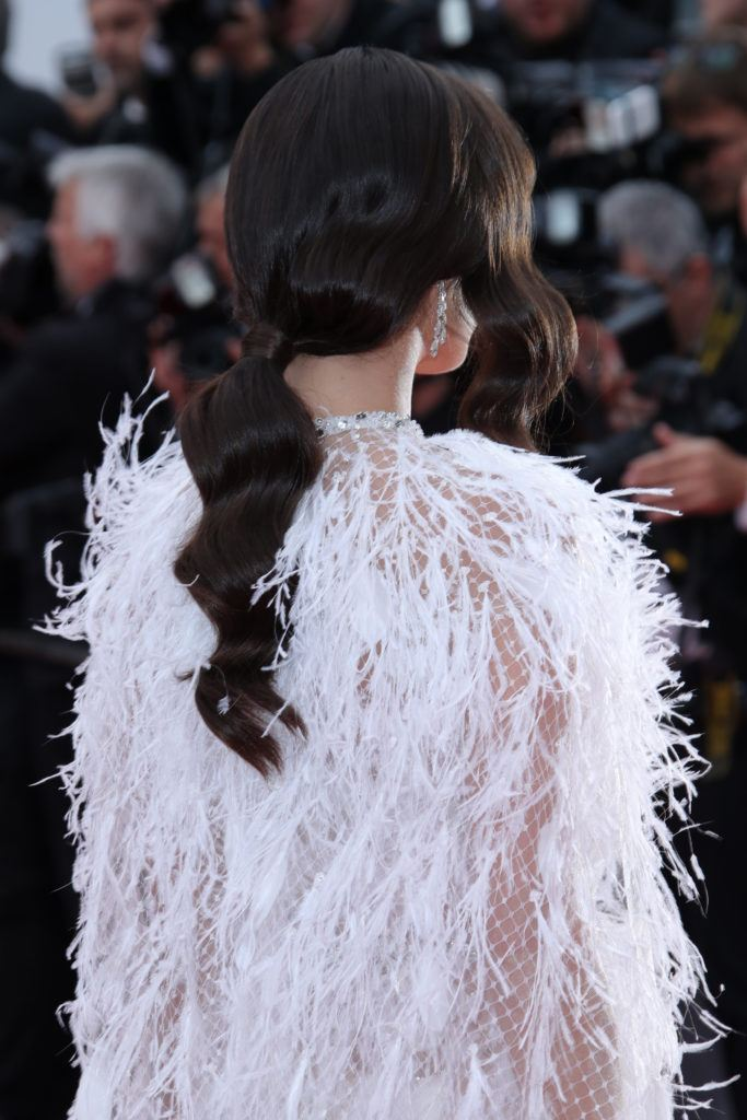 Vintage hairstyles for long: Back shot of Sara Sampaio with long chocolate brown hair styled into a vintage wavy ponytail wearing a feathered jacket on the red carpet