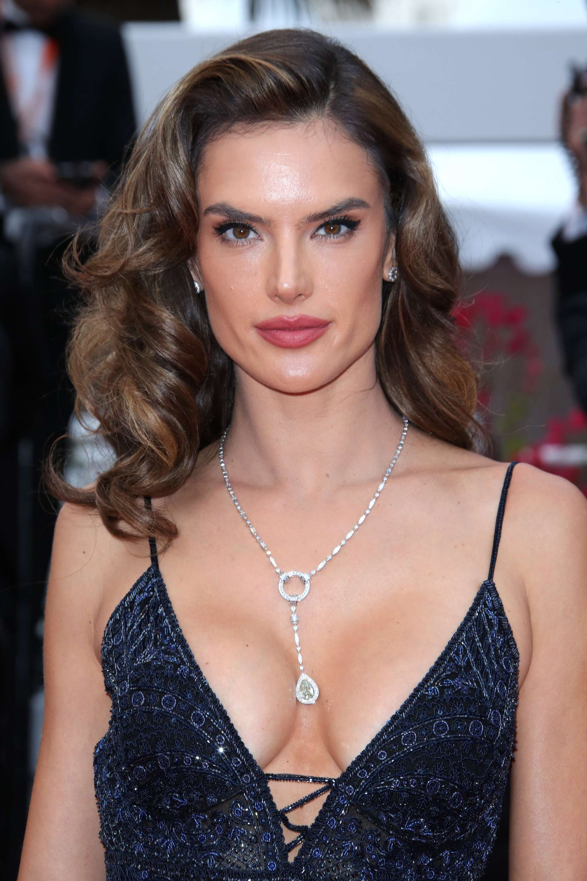 Vintage hairstyles for long hair: Close up shot of Alessandra Ambrosio with long chestnut brown styled into retro Hollywood waves, wearing midnight blue dress on the red carpet