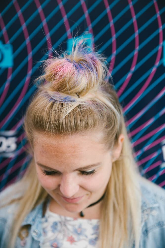 woman with half up bun decorated with multi coloured glitter