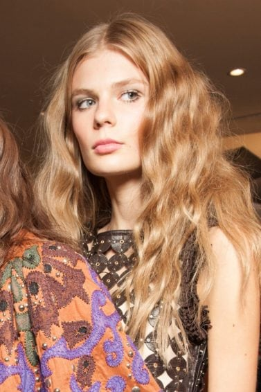 Wavy Hair Products: two models backstage one brunette and one blonde both with long wavy hair