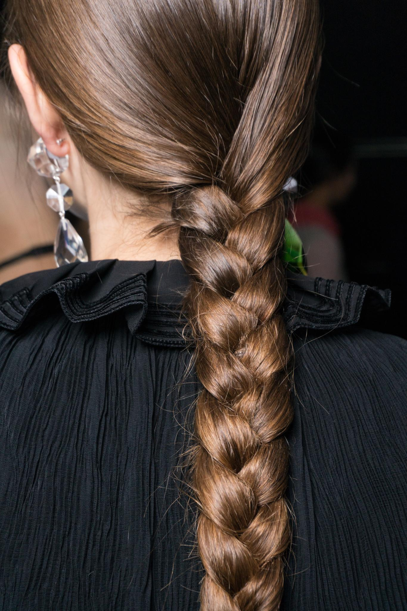 Thick hair: Shot of a model with long braided hair, wearing all black backstage
