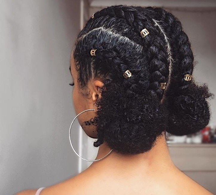 festival braids: close up shot of a model with natural dark hair braided into low space buns, complete with hair cuffs,posing in a bedroom setting