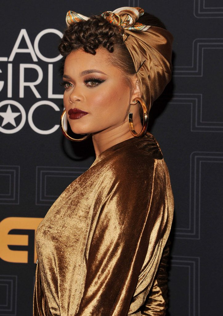 Vintage short hair: Close up shot of Andra Day with her short hair wrapped in a scarf, with a fake curly fringe at the front on the red carpet
