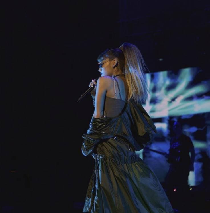 ariana grande on stage performing with her hair worn in her signature high ponytail style