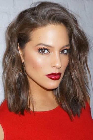 Ashley Graham with short wavy bob hair with a red top and red lipstick