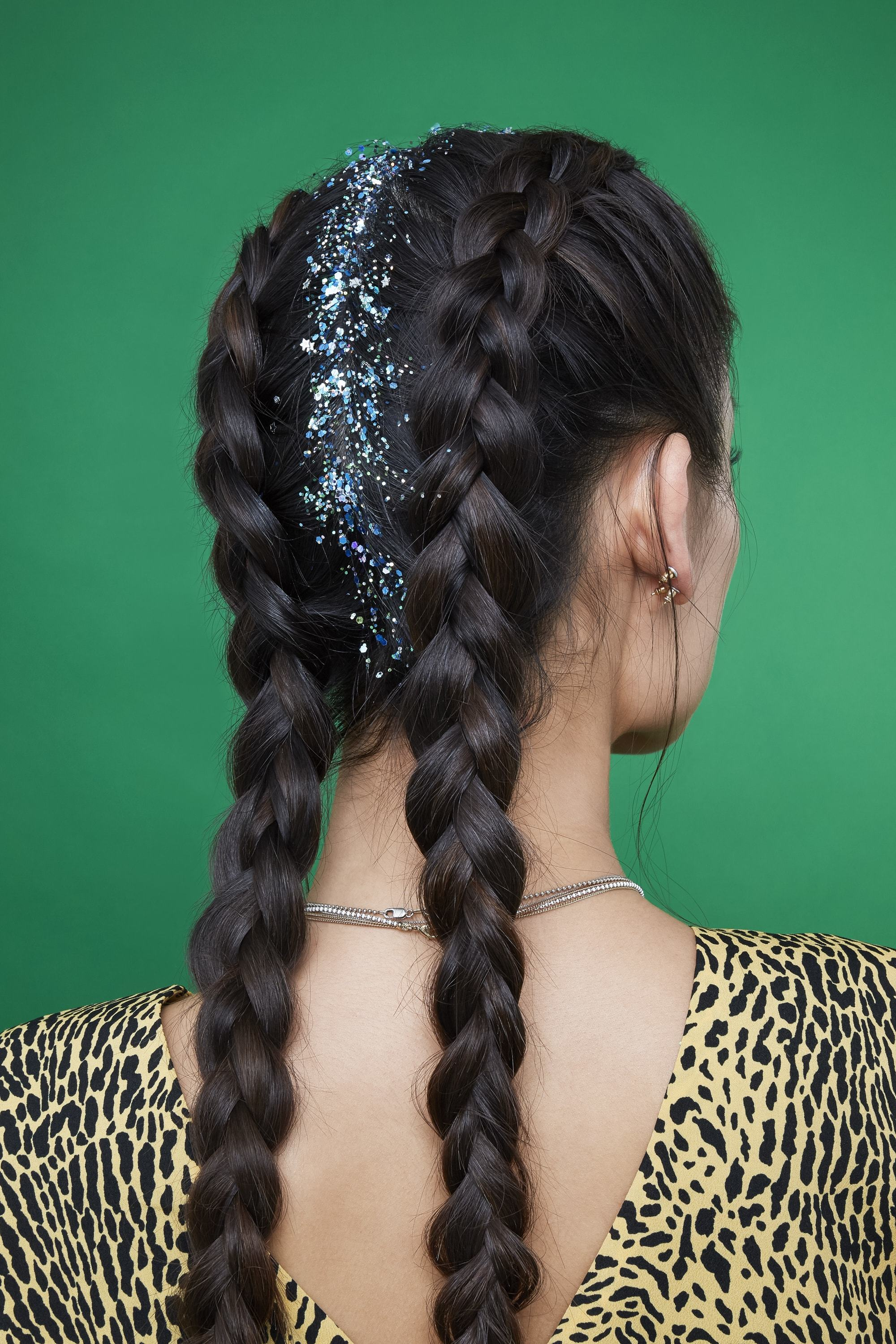 glitter roots how to: back shot of woman with glitter roots in her dark chocolate brown hair, fashioned into boxer braids and decorated with silver blue glitter roots, wearing a leopard print festival outfit